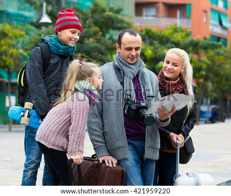 Smiling parents with two children and baggage using urban map  - stock photo