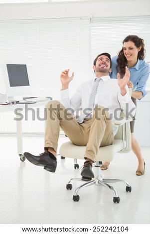 Smiling partners playing together with swivel chair in the office - stock photo
