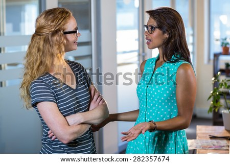 Smiling partners speaking together in the office - stock photo