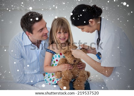 Smiling patient examining a teddy bear with a doctor against snow - stock photo