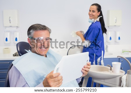 Smiling patient holding a mirror with a dentist behind him - stock photo