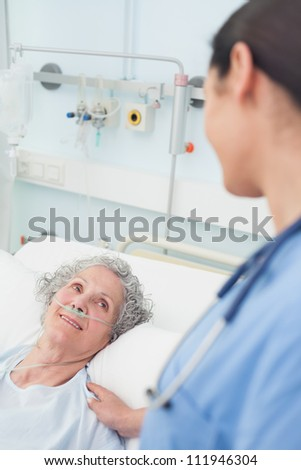 Smiling patient looking at a nurse in hospital ward - stock photo