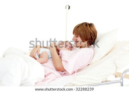Smiling patient with newborn baby in bed in hospital