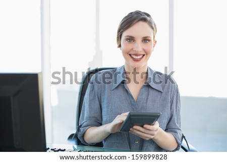 Smiling peaceful businesswoman using a calculator sitting at her desk smiling at camera - stock photo
