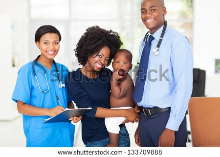 smiling pediatric medical professionals with african mother holding her baby