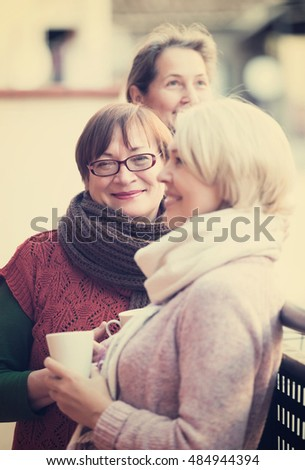 Smiling pensioners in warm clothes having cup of hot tea on terrace