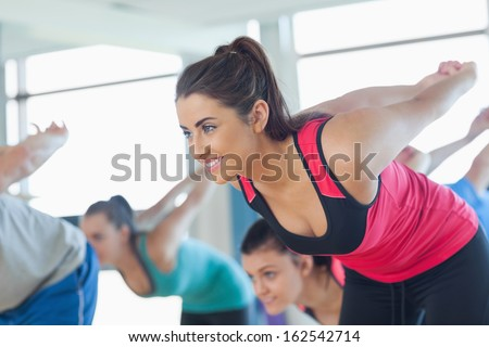 Smiling people doing power fitness exercise at yoga class in fitness studio - stock photo
