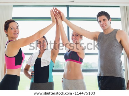 Smiling people high fiving each other in fitness studio in gym