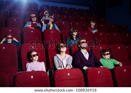 Smiling people in 3D movie theater - stock photo