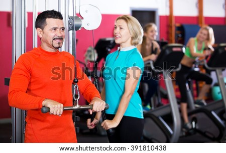 Smiling people of different age having strength training in gym