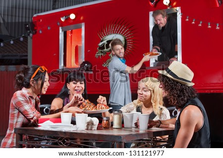 Smiling people sharing pizza and ordering food from canteen