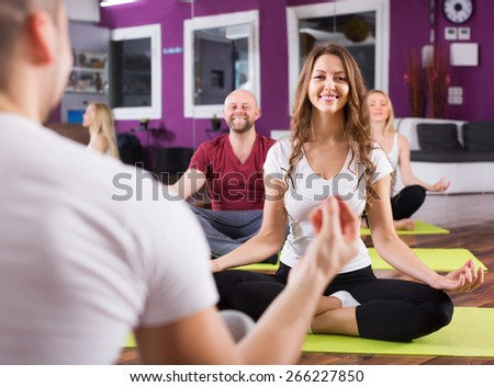 Smiling people studying new position at yoga school - stock photo