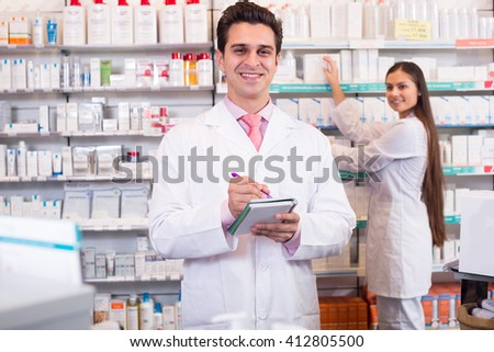 Smiling pharmacist and pharmacy technician posing in drugstore