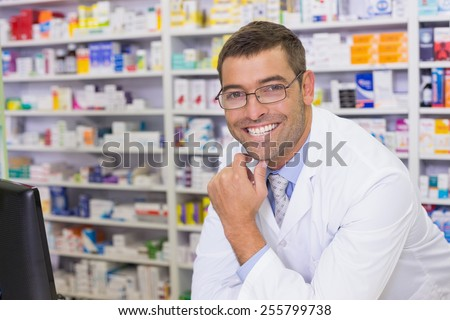 Smiling pharmacist looking at camera at the hospital pharmacy