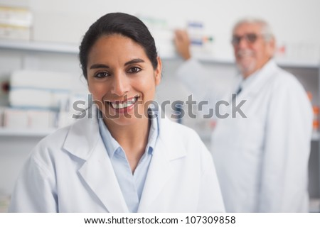 Smiling pharmacist looking at camera in hospital - stock photo