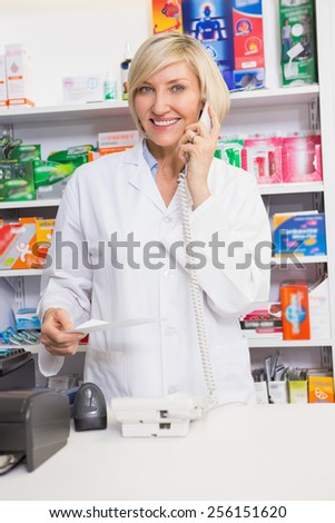 Smiling pharmacist on the phone reading prescription in the pharmacy