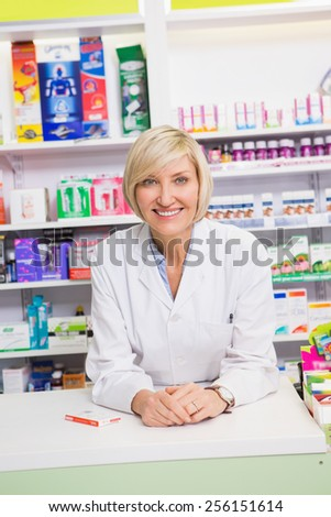 Smiling pharmacist posing behind the counter in the pharmacy