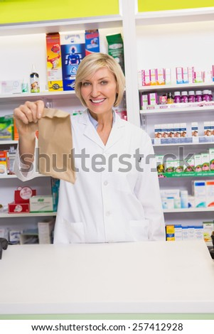 Smiling pharmacist showing envelope at the camera in the pharmacy