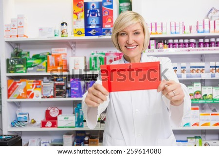 Smiling pharmacist showing envelope at the camera in the pharmacy - stock photo