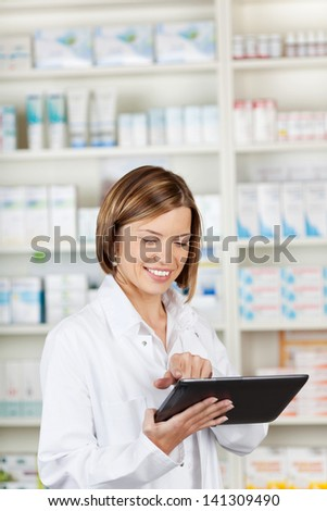 Smiling pharmacist using a tablet-pc scrolling with her finger on the touchscreen while standing in front of shelves of medication - stock photo