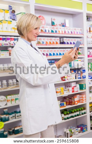 Smiling pharmacist using tablet pc in the pharmacy