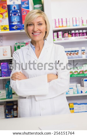 Smiling pharmacist with arms crossed in the pharmacy