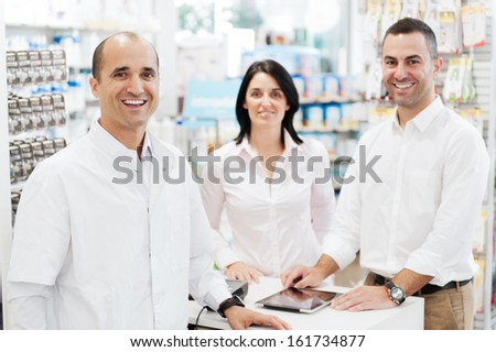 Smiling pharmacist with two customers in a pharmacy