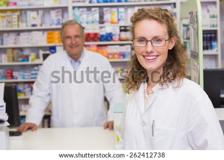 Smiling pharmacists looking at camera at pharmacy