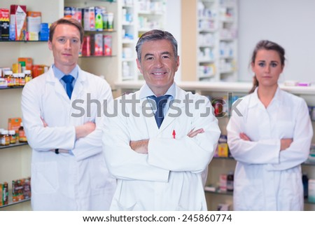 Smiling pharmacy team standing with arms folded in the pharmacy - stock photo