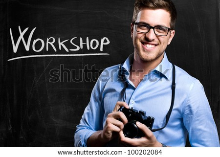 Smiling photographer in front of a blackboard - stock photo