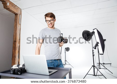 Smiling photographer using laptop computer in studio with eqipments - stock photo