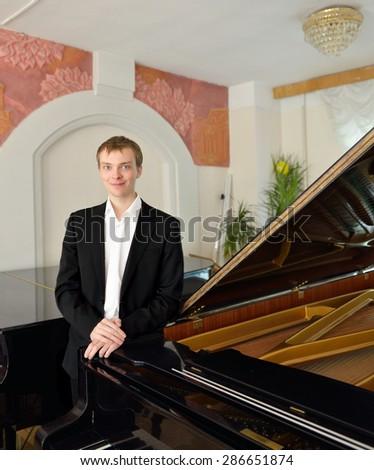 Smiling pianist next to black grand piano - stock photo