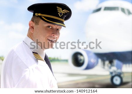 Smiling pilot goes into the plane - stock photo