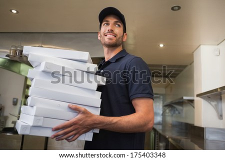 Smiling pizza delivery man holding many pizza boxes in a commercial kitchen - stock photo