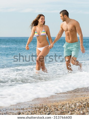 Smiling playful adult lovers couple having fun at sandy beach - stock photo
