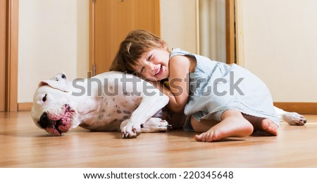 Smiling playful cute little girl hugging big white dog at home - stock photo