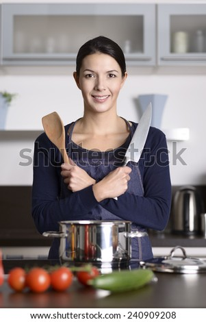 Smiling playful happy housewife preparing dinner posing with crossed arms holding a knife and wooden spoon as she stands at the counter in the kitchen spread with fresh vegetables - stock photo