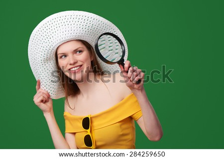 Smiling playful woman wearing bright yellow dress and summer straw hat looking through the magnifying glass at the blank copy space, over green background - stock photo