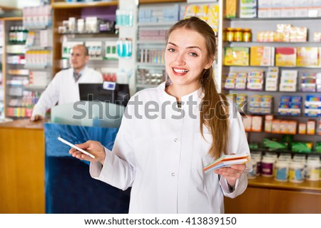 Smiling pleasant female pharmacist posing in drugstore