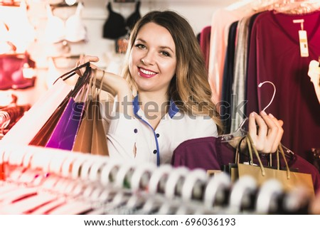 Smiling pleasant friendly female shopper boasting her purchases in underwear shop