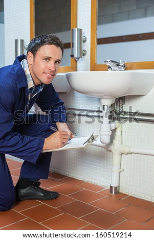 Smiling plumber inspecting sink holding clipboard in public bathroom