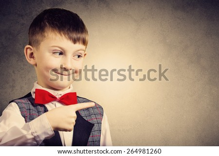 Smiling Pointing little boy isolated over grey background. - stock photo
