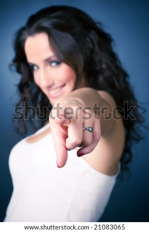 Smiling pointing woman. Focus on hand. - stock photo