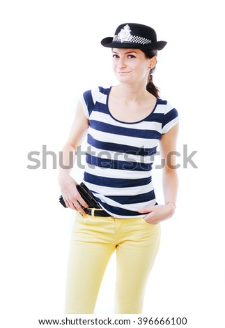 Smiling policewoman standing and holding a gun in the right hand - isolated on white. - stock photo