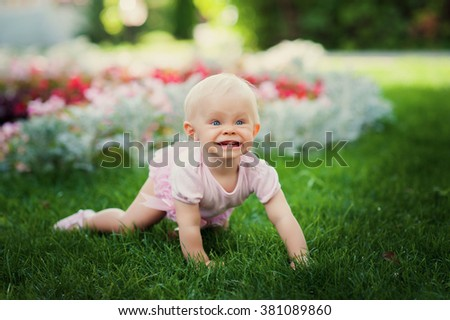 Smiling portrait cute baby-girl on green grass