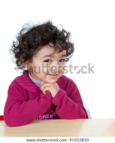 Smiling portrait of a Cute Baby Girl Sitting at a Desk, Isolated, White - stock photo