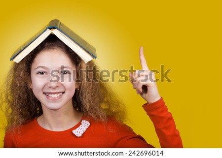 Smiling Portrait of a cute little schoolgirl loving to learn pointing up with a book on her head, isolated over yellow background.  - stock photo