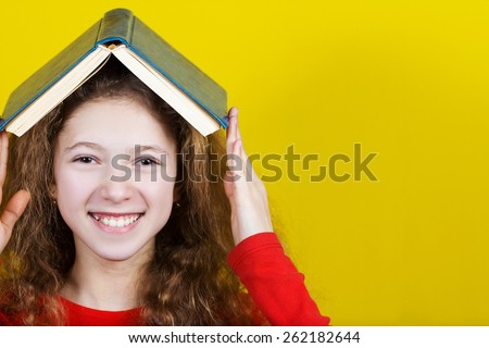 Smiling Portrait of a cute little schoolgirl loving to learn  with a book on her head, isolated over yellow background.  - stock photo