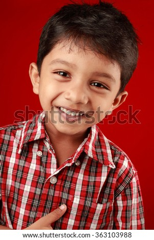Smiling portrait of a small boy in a red background - stock photo