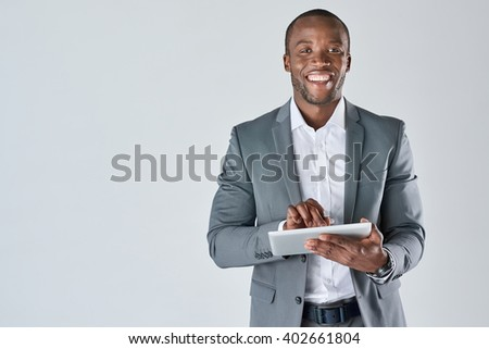 Smiling portrait of black businessman with touchscreen tablet device in business suit isolated in studio - stock photo